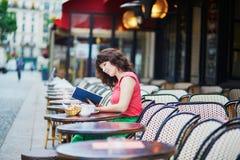Caffè bevente della donna e leggere un libro in caffè Immagini Stock