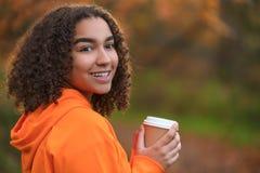 Caffè bevente della donna femminile dell'adolescente della corsa mista in autunno di caduta Immagine Stock