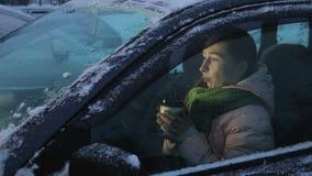 Caffè bevente della donna nell'automobile nell'inverno archivi video