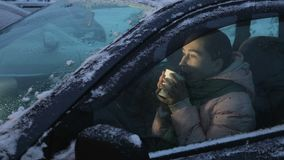 Caffè bevente della donna nell'automobile nell'inverno video d archivio