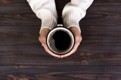 Caffè bevente della donna sola di mattina, vista superiore delle mani femminili che tengono tazza della bevanda calda sullo scrit Fotografie Stock Libere da Diritti