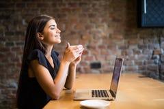 Caffè bevente della giovane bella donna alla barra del caffè davanti al computer portatile Immagini Stock