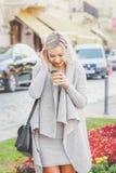 Caffè bevente della giovane donna alla moda sulla via Immagine Stock