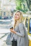 Caffè bevente della giovane donna alla moda sulla via Fotografie Stock Libere da Diritti