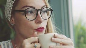 Caffè bevente della giovane donna emozionale in caffè Studentessa che scherza e che ride Ragazza che fa smorfie archivi video