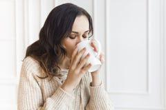 Caffè bevente della giovane donna graziosa di mattina Fotografie Stock