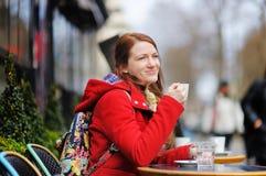 Caffè bevente della giovane donna in un caffè della via fotografia stock