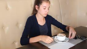 Caffè bevente della ragazza e comunicare sul telefono archivi video