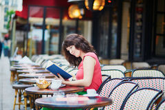 Caffè bevente della ragazza e leggere un libro in caffè parigino Fotografia Stock Libera da Diritti
