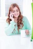 Caffè bevente della ragazza splendida e parlare sul telefono fotografie stock libere da diritti