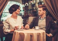 Caffè bevente delle coppie alla moda in ristorante fotografia stock libera da diritti