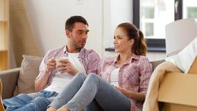 Caffè bevente delle coppie felici che si muove verso la nuova casa stock footage