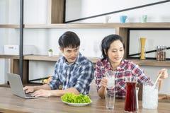 Caffè bevente delle giovani coppie adorabili asiatiche con latte in cucina a casa fotografia stock
