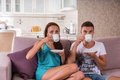 Caffè bevente delle giovani coppie sul sofà a casa Fotografia Stock