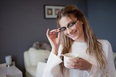 Caffè bevente di mattina della ragazza felice e bella a casa Giovane donna con sorridere di vetro Immagine Stock