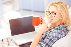 Caffè bevente di signora davanti al computer portatile Fotografie Stock