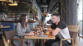 Caffè bevente donna e dell'uomo graziosi di sport e rilassarsi nello stile orientale del caffè Prima colazione, mattina piacevole video d archivio