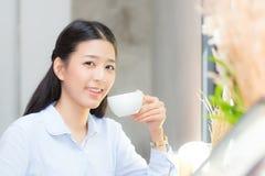 Caffè bevente e sorriso della bella giovane donna asiatica di mattina al caffè Immagine Stock Libera da Diritti