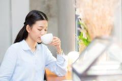 Caffè bevente e sorriso della bella giovane donna asiatica di mattina al caffè Fotografia Stock