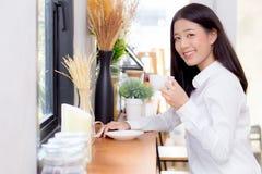 Caffè bevente e sorriso della bella giovane donna asiatica di mattina al caffè Immagini Stock Libere da Diritti