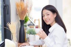 Caffè bevente e sorriso della bella giovane donna asiatica di mattina al caffè Immagine Stock