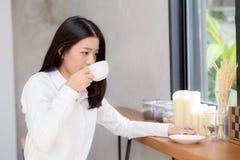 Caffè bevente e sorriso della bella giovane donna asiatica di mattina al caffè Fotografie Stock
