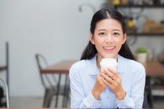 Caffè bevente e sorriso della bella giovane donna asiatica di mattina al caffè, alla ragazza che si siedono nella caffetteria per Immagine Stock
