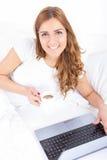 Caffè bevente sorridente della donna che si trova sul letto facendo uso del computer portatile Immagini Stock Libere da Diritti