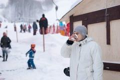 Caffè bevente stante del giovane ad una stazione sciistica Immagine Stock Libera da Diritti