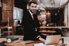 Caffè bevente Vestito di affari Computer portatile siedasi fotografia stock libera da diritti