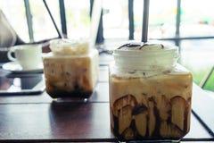 Caffè, caffè ghiacciato sul fondo di legno della tavola in caffè, in o anteriore Fotografie Stock Libere da Diritti