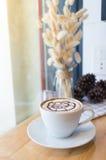 Caffè caldo con arte del latte della schiuma durante l'ora lavorativa Fotografia Stock