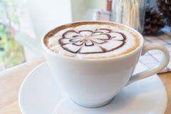 Caffè caldo con arte del latte della schiuma sullo scrittorio di legno Immagine Stock