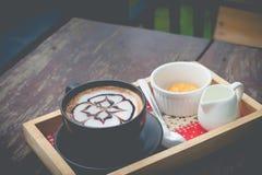 Caffè caldo con arte del latte della schiuma Tazza di caffè nera Fotografie Stock