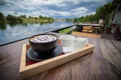 Caffè caldo con arte del latte della schiuma Tazza di caffè nera Immagini Stock