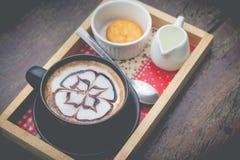 Caffè caldo con arte del latte della schiuma Tazza di caffè nera Fotografia Stock