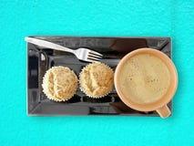 Caffè caldo con i bigné della banana sul piatto nero sul fondo blu della tavola del cemento Immagini Stock