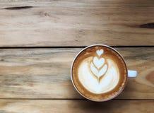 Caffè caldo del cappuccino in tazza bianca sul fondo di legno della tavola Arte del disegno della schiuma del latte immagini stock