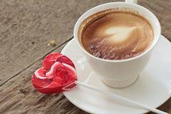 Caffè caldo del latte nel cuore dolce dei biglietti di S. Valentino della caramella e di vetro Fotografia Stock