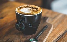 Caffè caldo del Latte sul piattino di legno fotografia stock libera da diritti