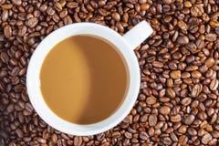 Caffè caldo delizioso con crema sui chicchi di caffè 1 Immagine Stock