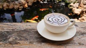 Caffè caldo di arte del latte sulla tavola di legno accanto allo stagno di pesce della carpa nello stile giapponese del giardino Immagini Stock Libere da Diritti