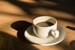 caffè caldo in tazza bianca sul sole e sull'ombra di legno di pomeriggio della tavola fotografie stock
