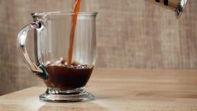 Caffè che è versato nella tazza trasparente video d archivio