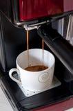 Caffè che cade dalla macchina di caffè espresso Fotografia Stock
