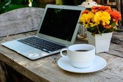 Caffè, computer portatile sul pavimento di legno con il fiore Fotografia Stock Libera da Diritti
