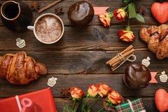 Caffè con cannella, regali, fiori sulla tavola di legno fotografie stock