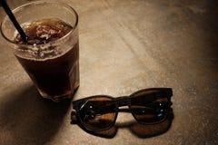 Caffè con gli occhiali da sole di legno sull'anca di rilassamento di tempo della superficie di metallo Fotografia Stock