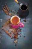 Caffè con i chicchi di caffè e della cannella su un fondo scuro Fotografie Stock