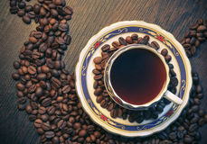 Caffè con i chicchi di caffè su fondo di legno con la tazza dall'orizzontale di angolo superiore Immagine Stock Libera da Diritti